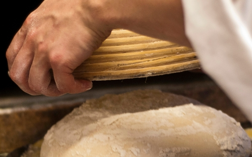 Chefs hands turning out bread dough from a basket